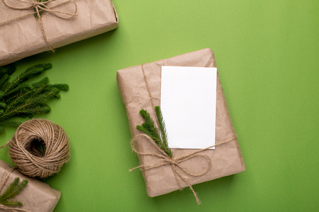 Eco present and card with green plants in craft paper on a green background top view