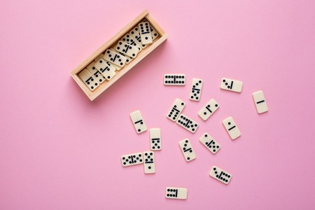 Board game of dominoes with a wooden case on a pink background top view Imagens