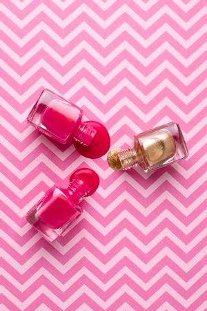 Cosmetic pink and gold nail polishes on a pink background