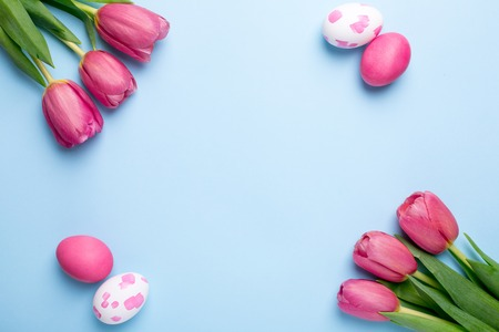 Pink flowers tulips and easter eggs on a blue background top view