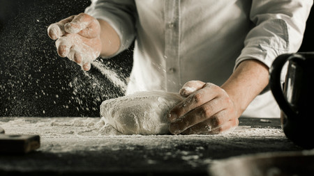 Male chef hands knead dough with flour on kitchen table side view Фото со стока
