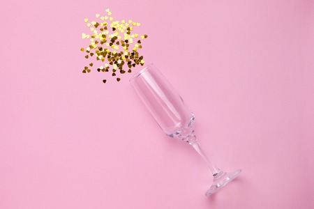 Champagne glass with golden confetti on pink color paper background minimal style Stock fotó