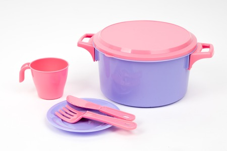 Plastic children's dishes pink and lilac colour on a white background isolated side view Stock Photo