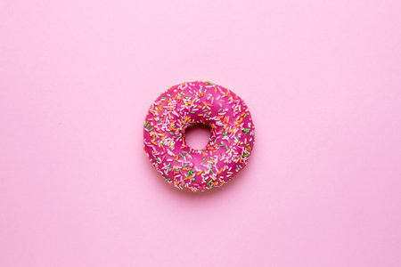 Sweet pink donut with multicolored sprinkles on a pink background flat lay