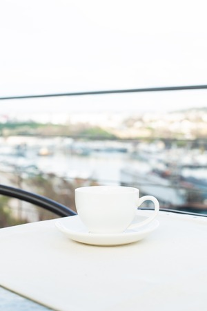 White ceramic cup with saucer on the table outdoor on the background of the city