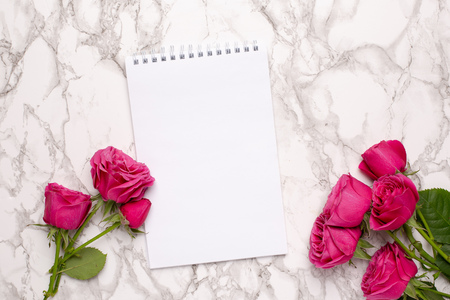 Pink roses and white notebook on a marble background top view