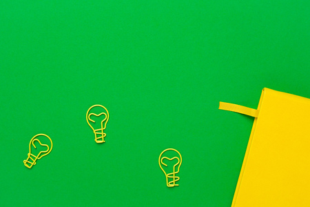Notebook with blank pages and paperclip light bulb idea on green background. Summer colour flatlay top view 免版税图像
