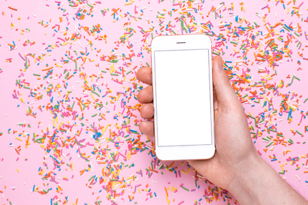Male hands hold mobile phone mock up on a pink background with sweet multicolored sprinkles top view