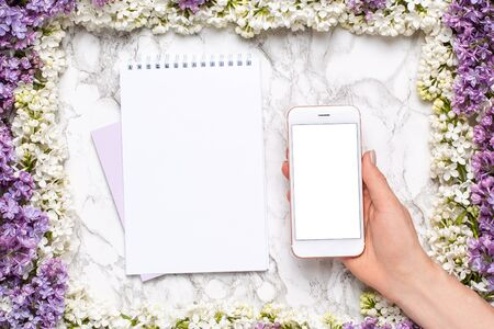 Mobile phone mock up in hand, notebook and frame of white and lilac flowers on marble table in flat lay style top view.