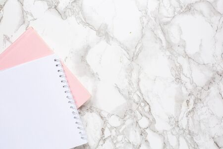 Marble background with white and pink notebook top view. Women business day