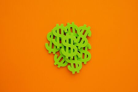 American dollar symbol on orange background. Green money top view Standard-Bild