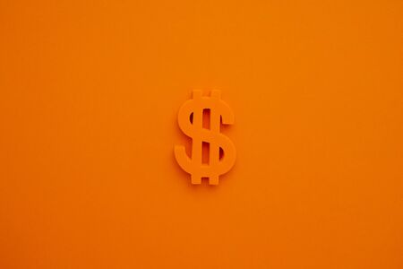 American dollar symbol on orange background top view.