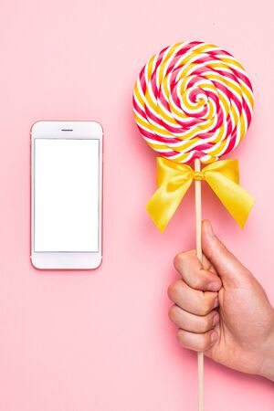 Mobile phone and colorful lolipop with pink, yellow and white spiral in hand on pink background top view