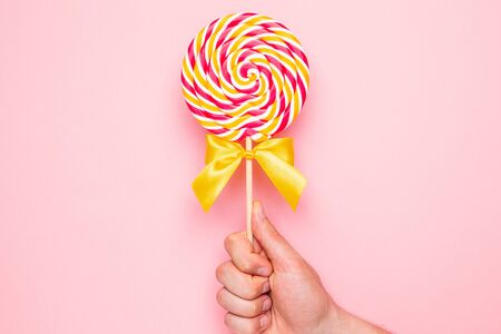 Colorful lolipop with pink, yellow and white spiral in hand on pink background top view Zdjęcie Seryjne