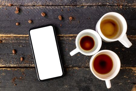 Mobile phone mock up and white empty coffee cups.Composition for coffee shop and coffee top view