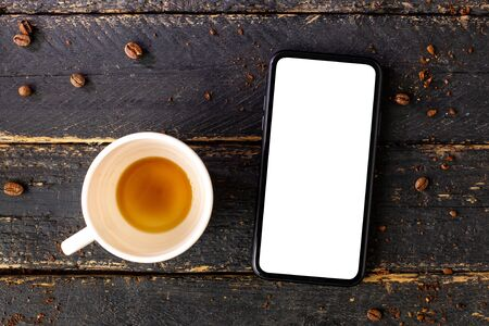 Mobile phone mock up and white empty coffee cup.Composition for coffee shop and coffee top view.