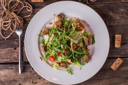 Meat with fresh herbs and cherry tomatoes on rustic table top view