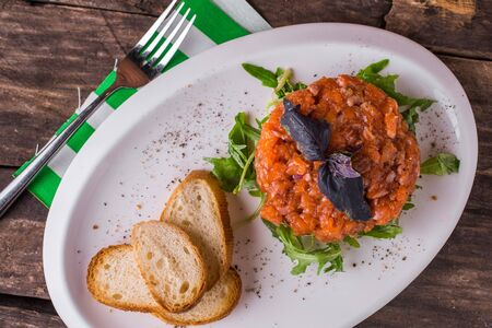 Salmon tartare with arugula and croutons rustic table top view