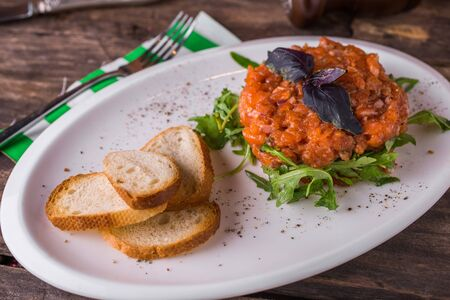 Salmon tartare with arugula and croutons rustic table side view