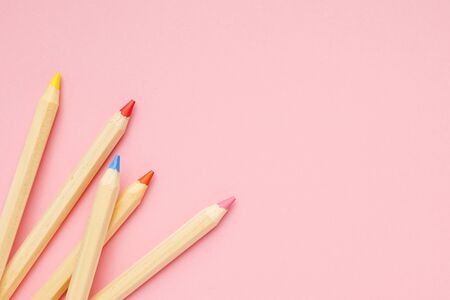 Pink background with wooden colorful ordinary pencils top view. Back to school.
