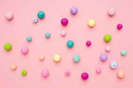Colorful pastel beads on pink background. Girly minimalist composition top view Zdjęcie Seryjne