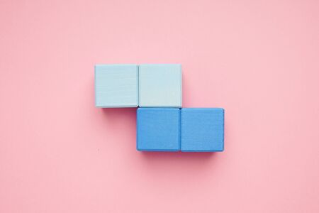 Colorful wooden cubes on pink background top view.Creativity toys. Childrens building blocks. Zdjęcie Seryjne