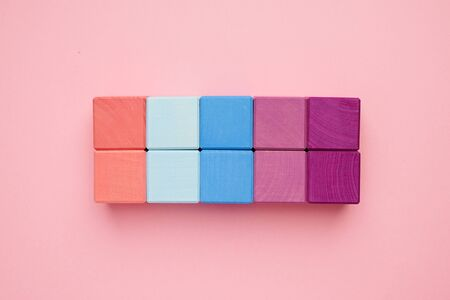 Colorful wooden cubes on pink background top view.Creativity toys. Childrens building blocks. Banco de Imagens