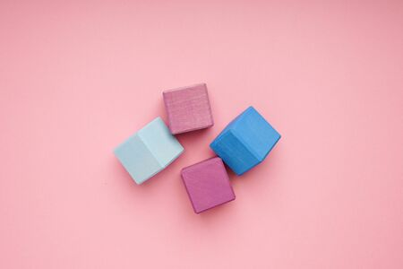 Colorful wooden cubes on pink background top view.Creativity toys. Childrens building blocks Zdjęcie Seryjne