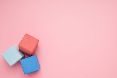 Pink background with colorful wooden cubes top view.Creativity toys. Childrens building blocks.
