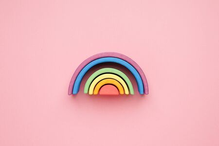 Multicolored wooden rainbow on pink background top view Stockfoto