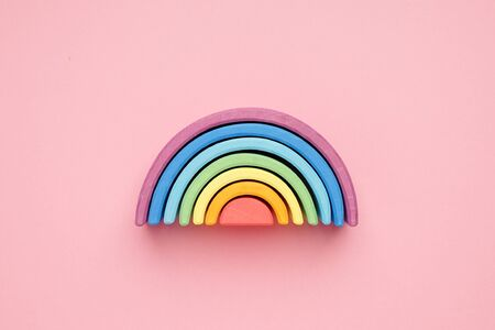 Colorful Waldorf wooden rainbow in a montessori teaching pedagogy on pink background top view