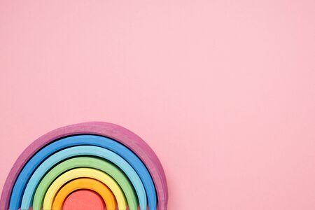 Pink background and Waldorf wooden rainbow in a montessori teaching pedagogy top view Zdjęcie Seryjne