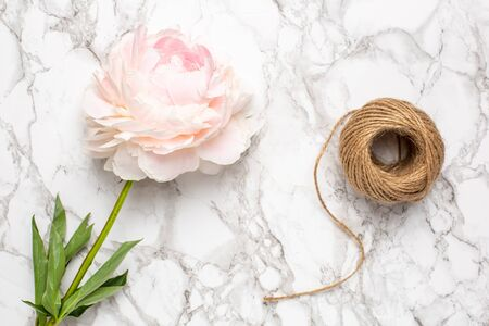 Pink flowers peony and twine on a marble background top view. Holiday and summer item. Zdjęcie Seryjne