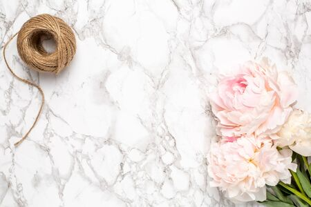 Marble background with pink flowers peony and twine top view Zdjęcie Seryjne