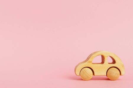 Wooden baby car on a pink pastel background with copyspace side view. Zdjęcie Seryjne