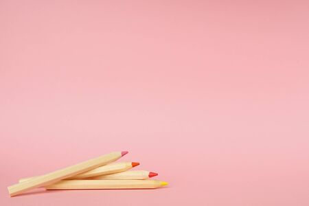 Pink background with wooden colorful ordinary pencils side view. Back to school.