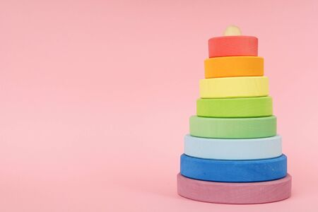 Childrens wooden multi-colored pyramid on a pink background side view