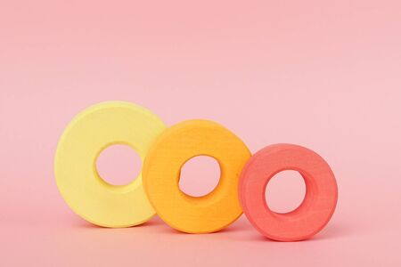 Childrens wooden rings of orange and yellow on a pink background side view