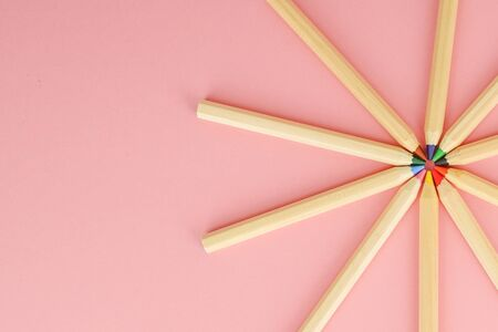 Pink background with wooden colorful ordinary pencils. Back to school.