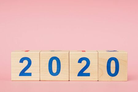 New year 2019 change to 2020 concept. Wooden block cube with number on pink table