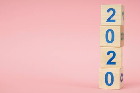 New year 2019 change to 2020 concept. Wooden block cube with number on pink background Zdjęcie Seryjne
