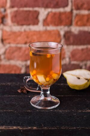 Tea with sea buckthorn and pear on a wooden table