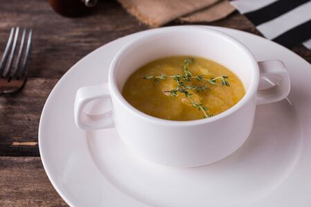 Vegetable cream soup with oregano in a white plate