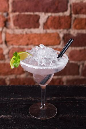 Martini cocktail with ice and lime on a background of a brick wall in a bar
