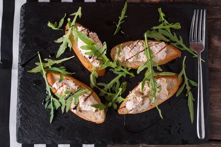 Bruschetta with curd and herbs on a stone board