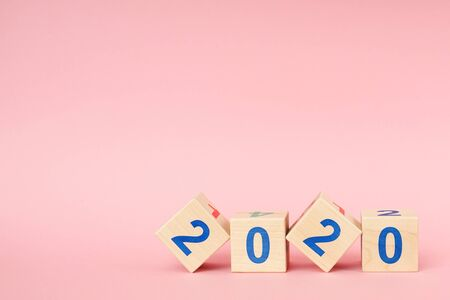 Wooden block cube with number New year 2020 on pink background Zdjęcie Seryjne