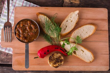 Bruschetta with vegetable sauce and hot pepper on a wooden board