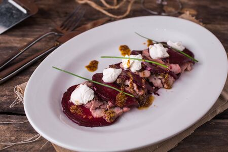 Restaurant meal veal with beetroot and cheese on wooden table