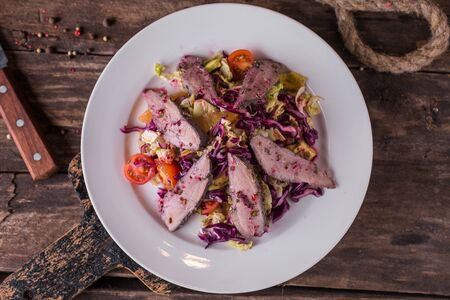 Salad with vegetables and meat in white restaurant plate Zdjęcie Seryjne