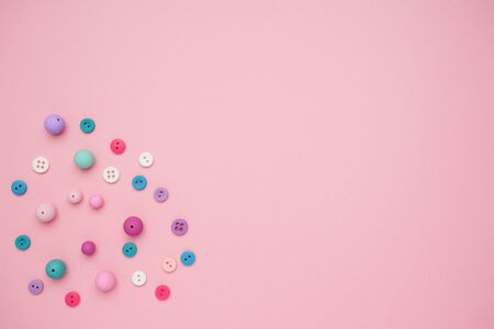 Collection of Colourful Sewing Buttons on Pink Background with Copy Space